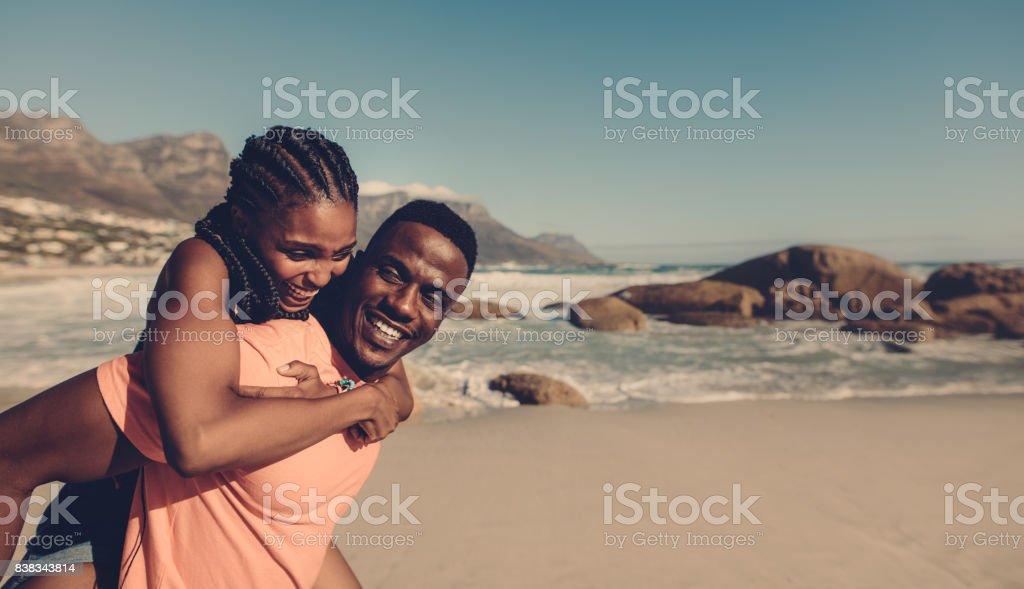 Pareja joven disfrutando en la playa - foto de stock