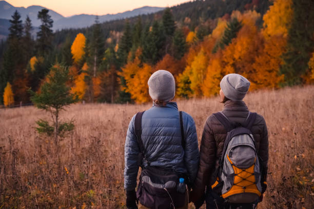 Young couple enjoying beautiful autumn forest in the mountains stock photo