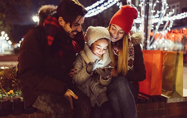 young couple enjoying christmas in the city - geschenke eltern weihnachten stock-fotos und bilder