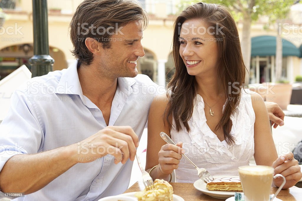 Young Couple Enjoying Coffee And Cake In Caf royalty-free stock photo