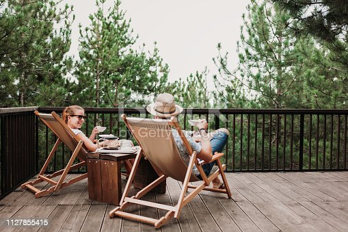 istock Young couple enjoying coffee on the balcony in the mountains 1127855415