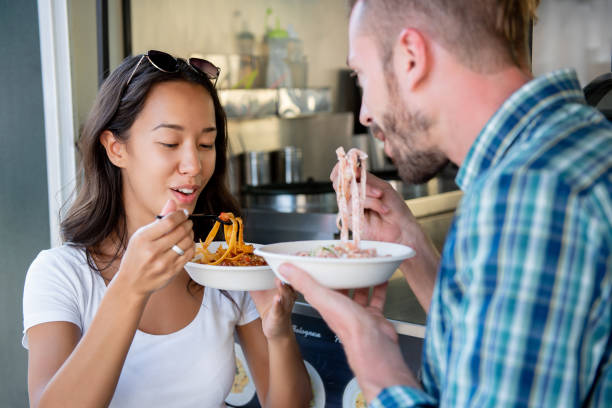 young couple enjoying eating pasta from food truck - being in a relationship with someone is going to require stock photos and pictures