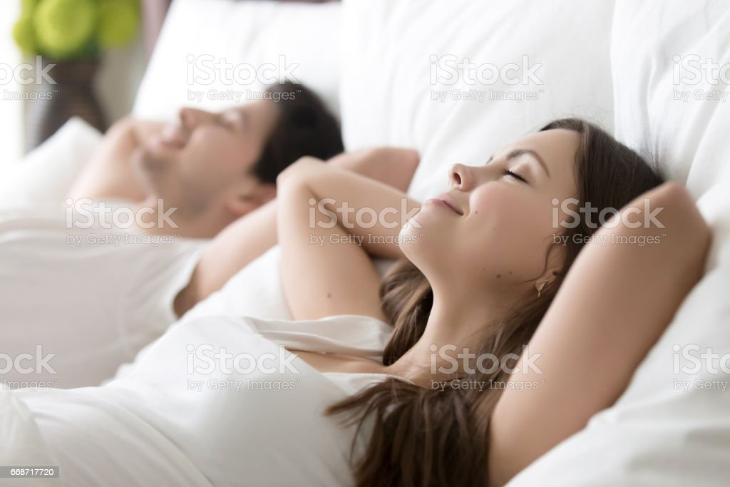 Young couple enjoying good morning in bed with eyes closed - foto de stock