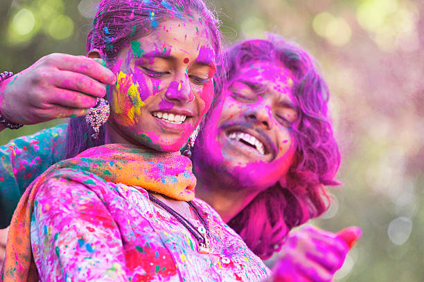 Young Couple Enjoying Holi Festival Young couple covered in colored dye enjoying Holi festival in Jaipur, India. romance stock pictures, royalty-free photos & images