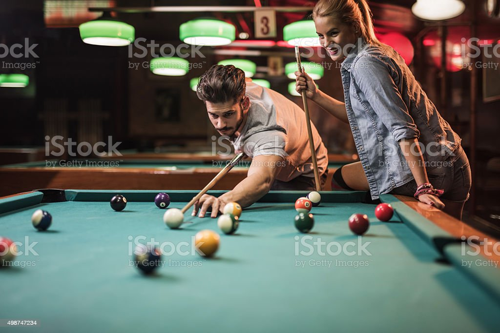 Young couple enjoying in a snooker game at pool hall. stock photo