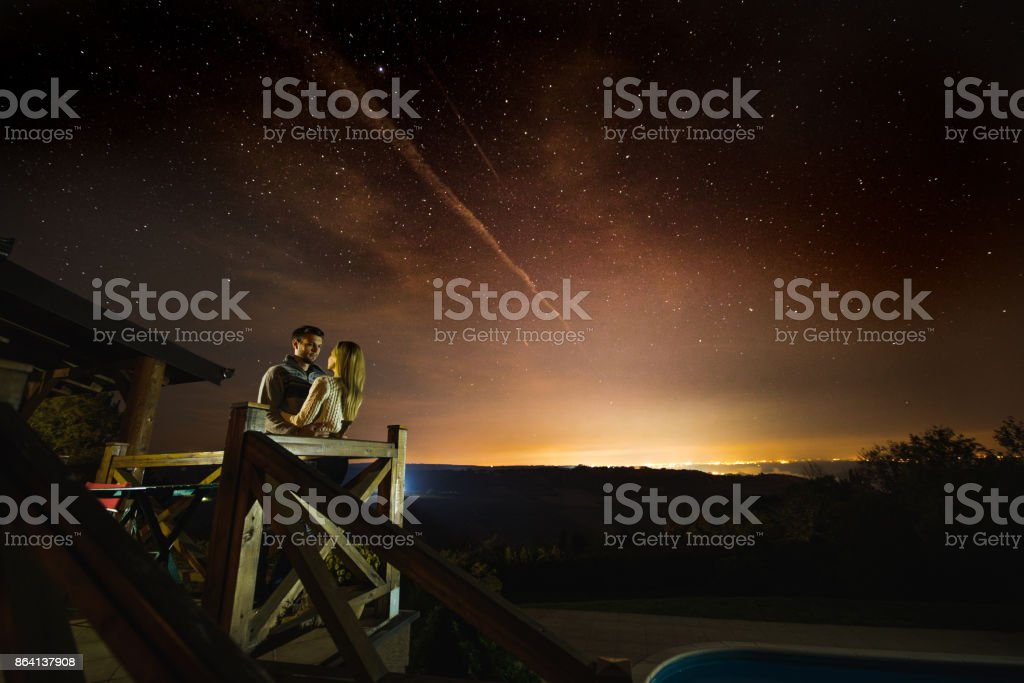 Young couple enjoying in romantic moments under starry sky. royalty-free stock photo