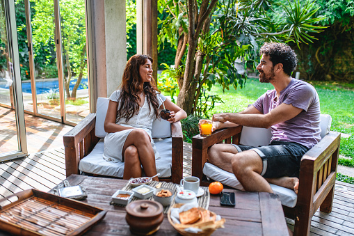 Hispanic and mixed race couple sitting outdoors on home deck and enjoying relaxing breakfast and conversation.