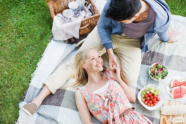 junges paar genießen ein picknick - romantisches picknick stock-fotos und bilder