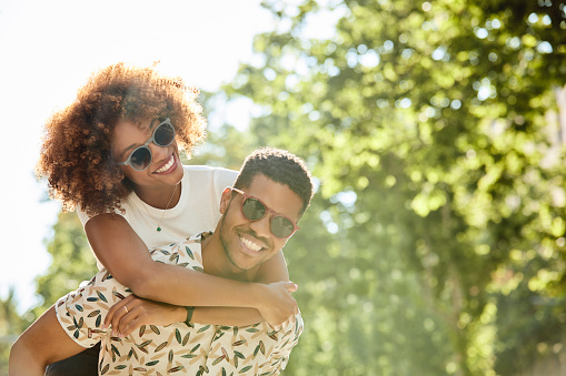 Young couple enjoying piggyback ride on sunny day. Smiling man and woman are spending leisure time in city. They are on vacation.