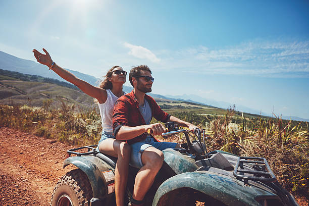 Young couple enjoying quad bike ride Happy young couple in nature on a quad bike. Young man and woman enjoying a quad bike ride in countryside. Man driving and woman enjoying the ride with her hands raised on a summer day. quadbike stock pictures, royalty-free photos & images