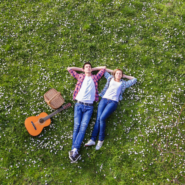 young couple enjoying springtime - reclining stock photos and pictures