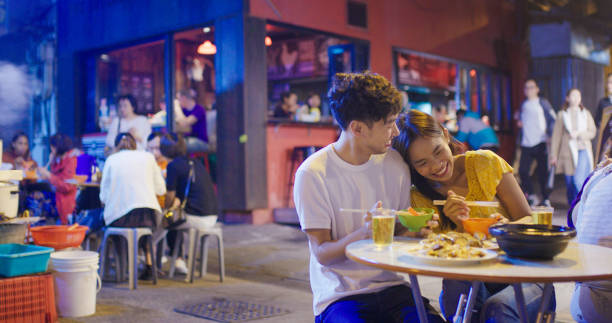 Young couple enjoying street food Young couple enjoying street food. Hong Kong 2019, Shot in 4K night market stock pictures, royalty-free photos & images