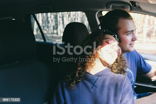 1030408008istockphoto Young couple enjoying sunset from car 956170330