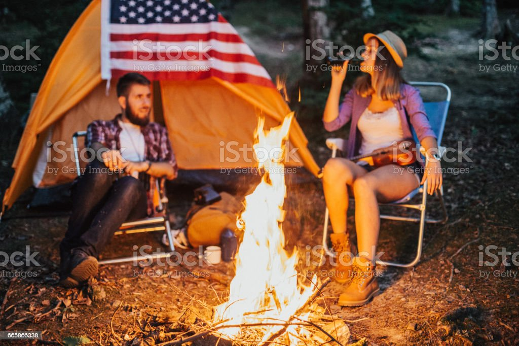 Young couple enjoying the warmth of the campfire stock photo
