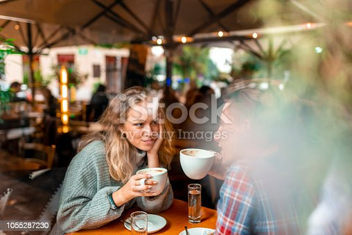 Young caucasian couple enjoying their coffee in a bar. View through the window.
