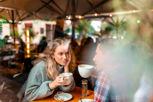 Young couple enjoying their coffee in a bar Young caucasian couple enjoying their coffee in a bar. View through the window. date stock pictures, royalty-free photos & images