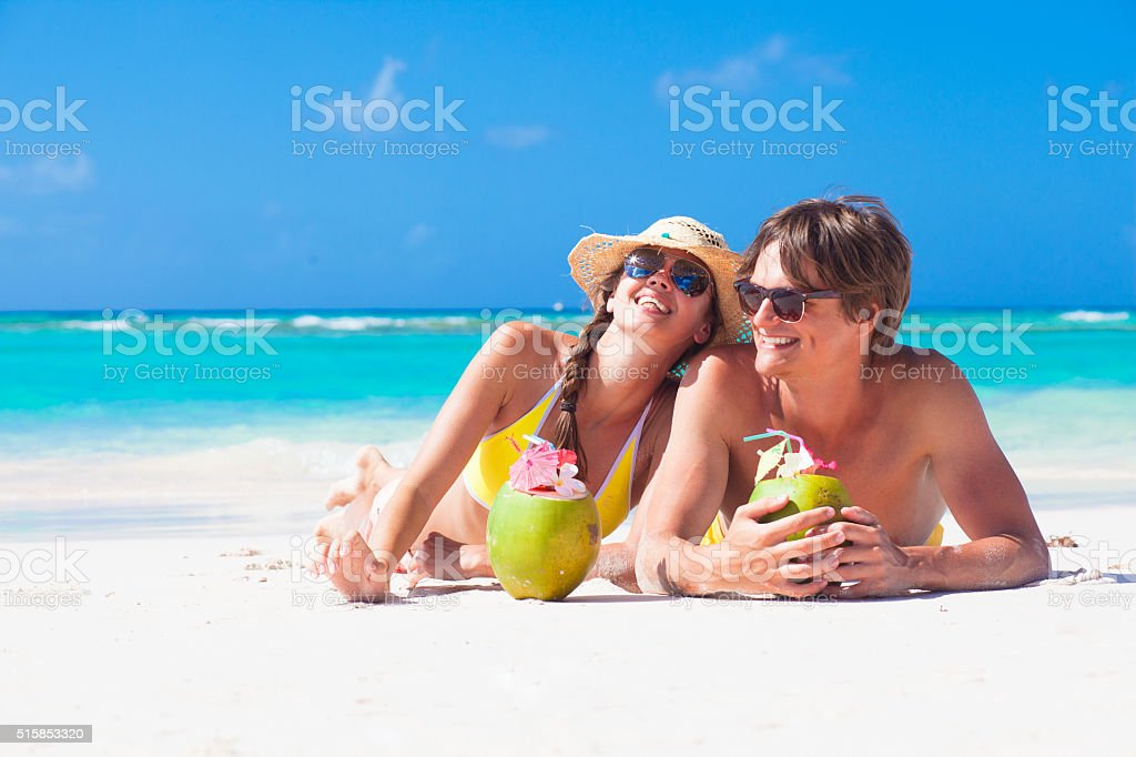 young couple enjoying their time drinking coconut cocktail stock photo