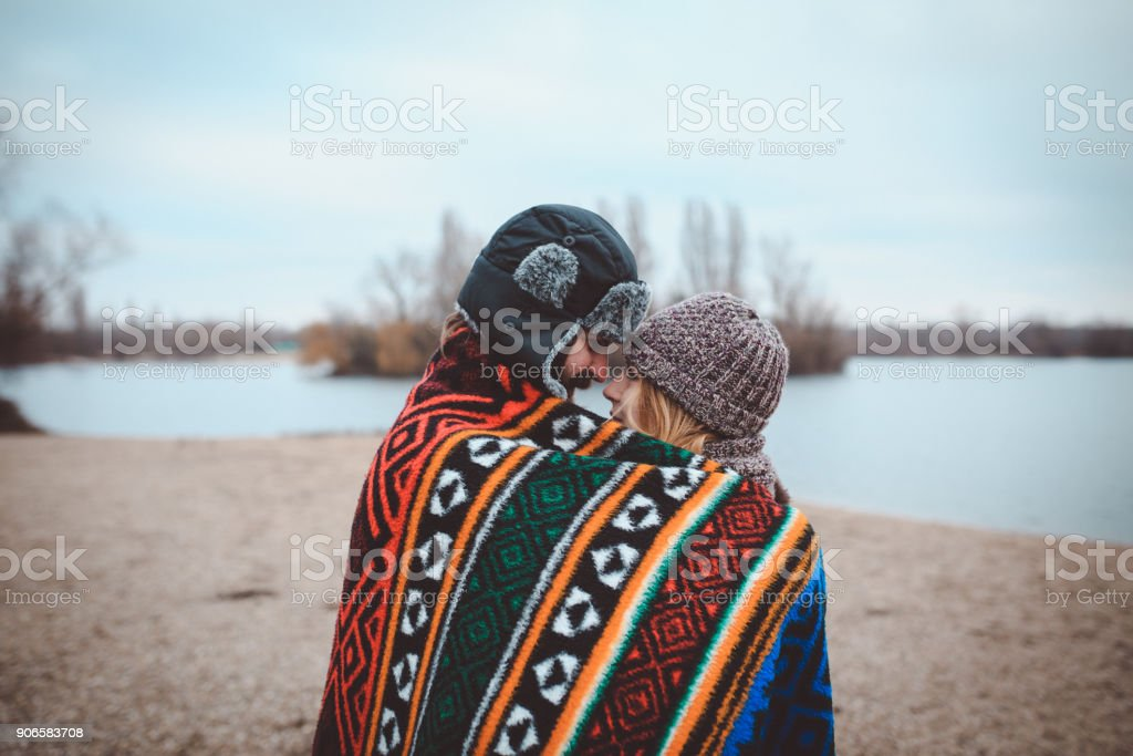 Young couple enjoying time near the lake on a lovely winter day stock photo