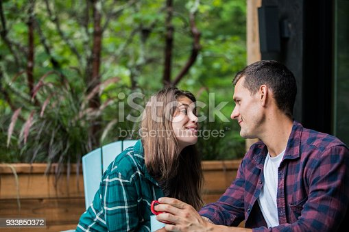 1083155024 istock photo A young couple enjoying vacations at the cabin. Drinking coffee and having a romantic conversation on the balcony 933850372