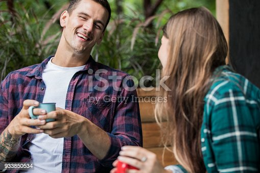 1083155024 istock photo A young couple enjoying vacations at the cabin. Drinking coffee and having a conversation on the balcony 933850534