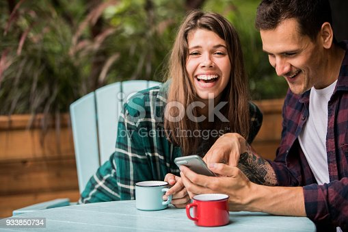 1083155024 istock photo A young couple enjoying vacations at the cabin. Having a conversation on the balcony and laughing 933850734