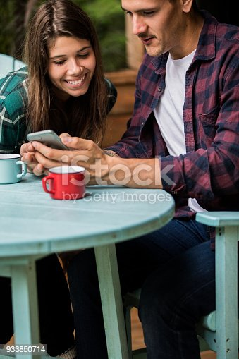 1083155024 istock photo A young couple enjoying vacations at the cabin. Looking at a smartphone and smiling 933850714