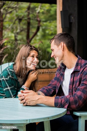 1083155024 istock photo A young couple enjoying vacations at the cabin. Looking at each other and having a conversation 933850564