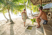Young couple enjoying vacations on tropical beach from bungalow, palm trees.. People travel vacations love concept. Shot in the Visayas Islands, Philippines