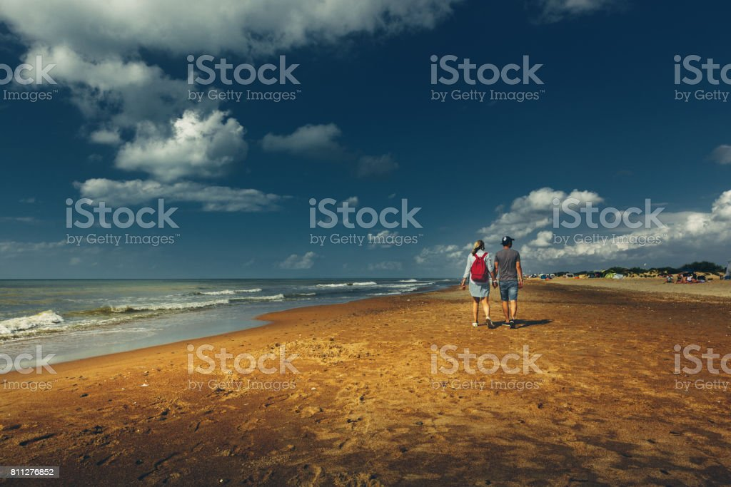 Young Couple Enjoyng Walking Along Sandy Shore, Rear View. Walking Hiking Journey Together Concept stock photo