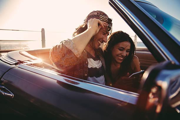 junges paar blick auf fotos auf smartphone auf einem cabrio - nostalgie telefon stock-fotos und bilder