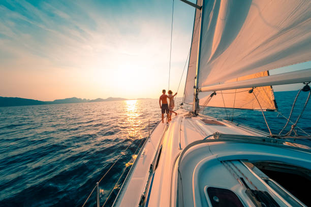 Young couple enjoys sailing in the tropical sea at sunset on their yacht. stock photo