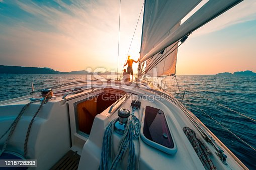 Young couple enjoys sailing in the tropical sea at sunset on their yacht.