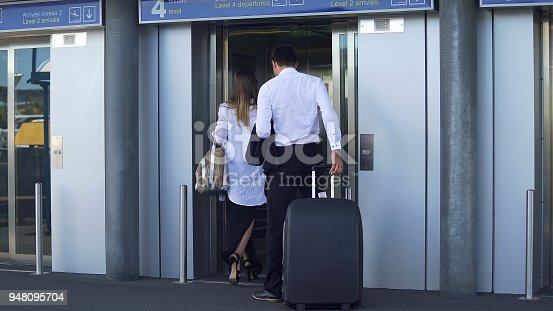 638591126istockphoto Young couple entering elevator at airport, business trip, travel and tourism 948095704
