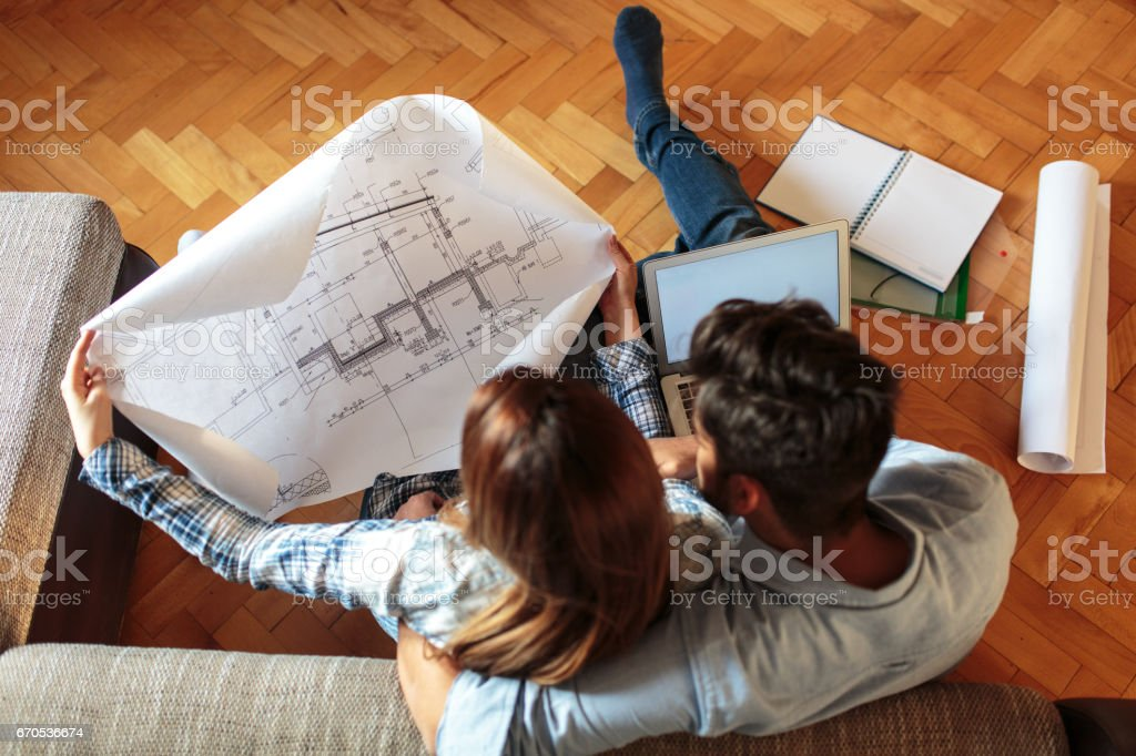 Young couple examining blueprints of they new home.Real estate and...