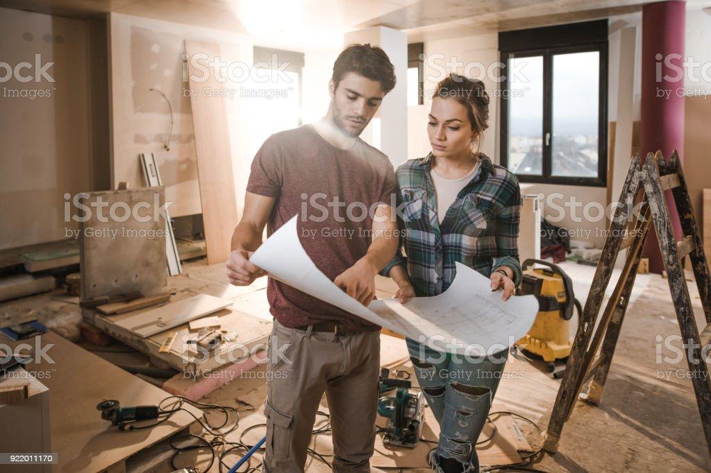 Junges Paar Baupläne selbst auf Baustelle in ihrer Wohnung zu prüfen. – Foto