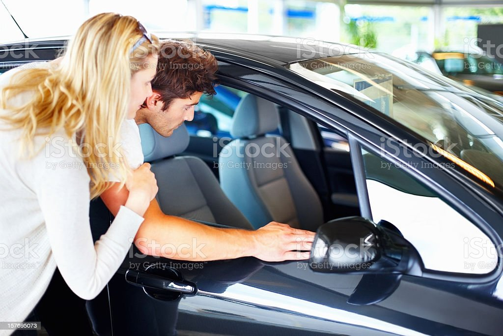 Young couple examining their new car in showroom royalty-free stock photo