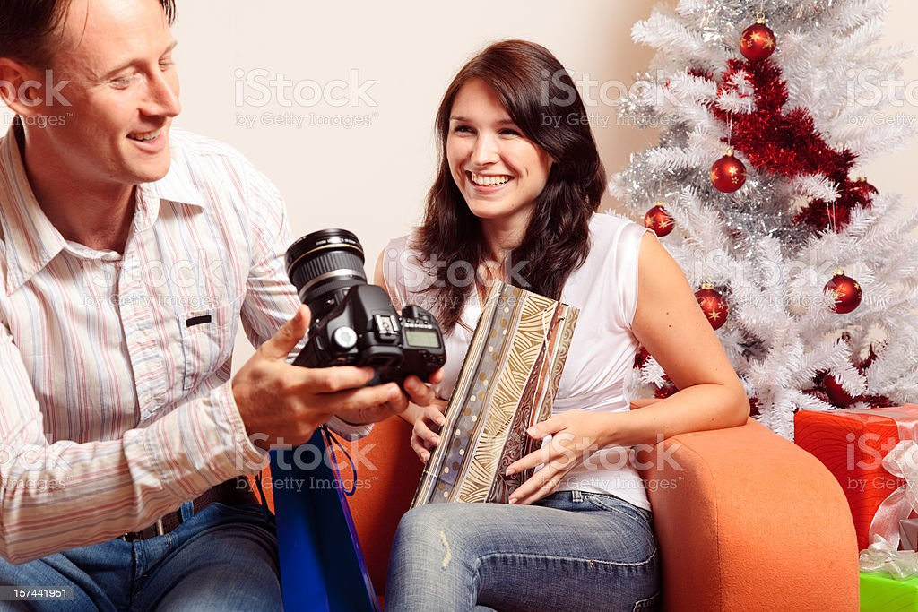young couple exchanging christmas gifts (series) royalty-free stock photo