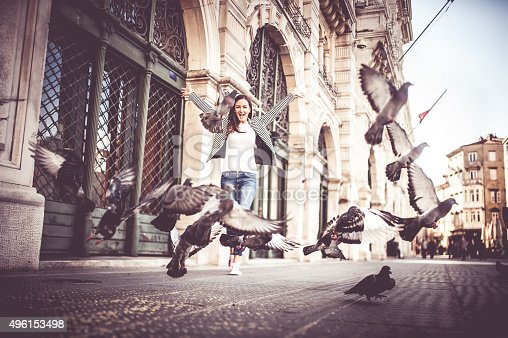 Young woman chasing pigeons outdoor