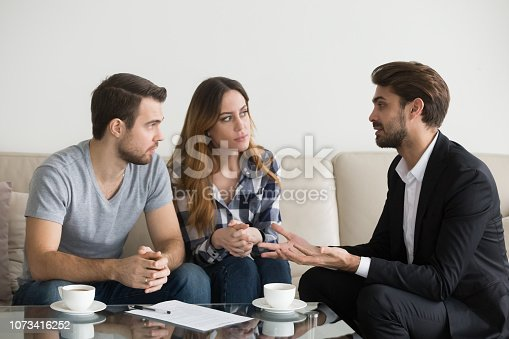 963814372istockphoto Young couple, family at meeting with realtor, interior designer 1073416252