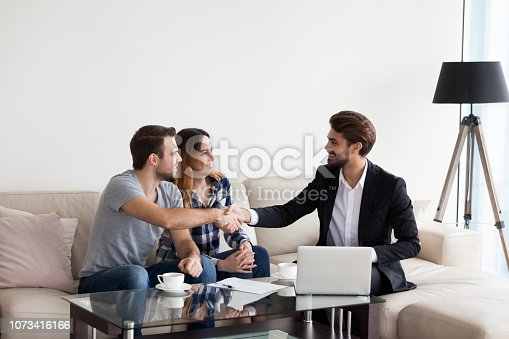 istock Young couple, family making deal with realtor, interior designer 1073416166