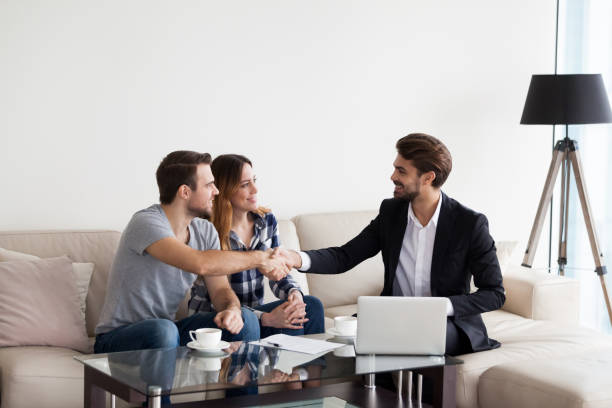 Young couple, family making deal with realtor, interior designer Young couple, family at meeting with realtor, interior designer, decorator, landlord making deal. Husband handshaking with man in suit. Concept of meeting with client, customer seller stock pictures, royalty-free photos & images