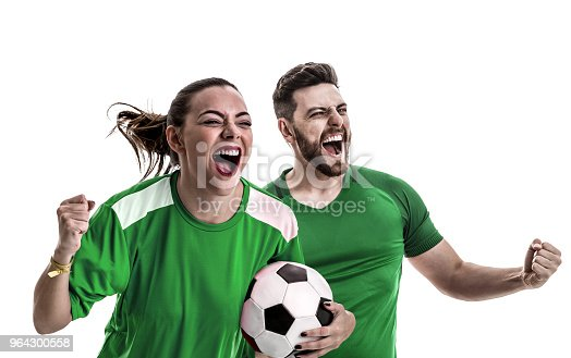 istock Young couple fan in green uniform celebrating 964300558