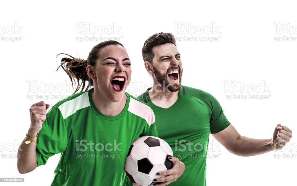 Ventilador de joven pareja en la celebración de uniforme verde - foto de stock