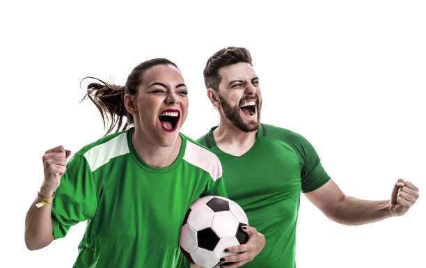 Young couple fan in green uniform celebrating Soccer passion american football league stock pictures, royalty-free photos & images