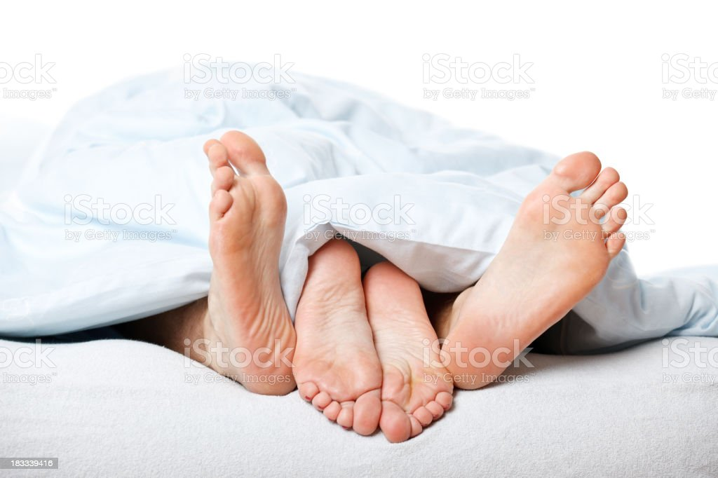 young couple feet in bed stock photo