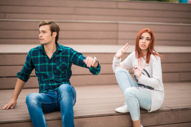 Young couple fighting while sitting on the stairs stock photo