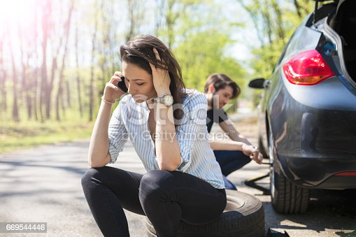istock Young couple flat tire on the road 669544446