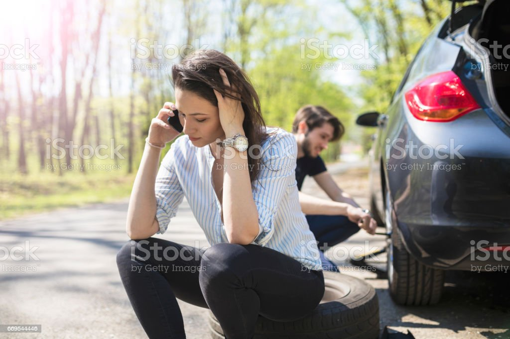 Young couple flat tire on the road stock photo