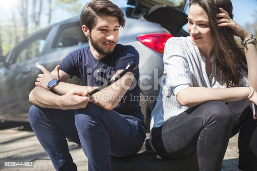 627511482 istock photo Young couple flat tire on the road 669544482