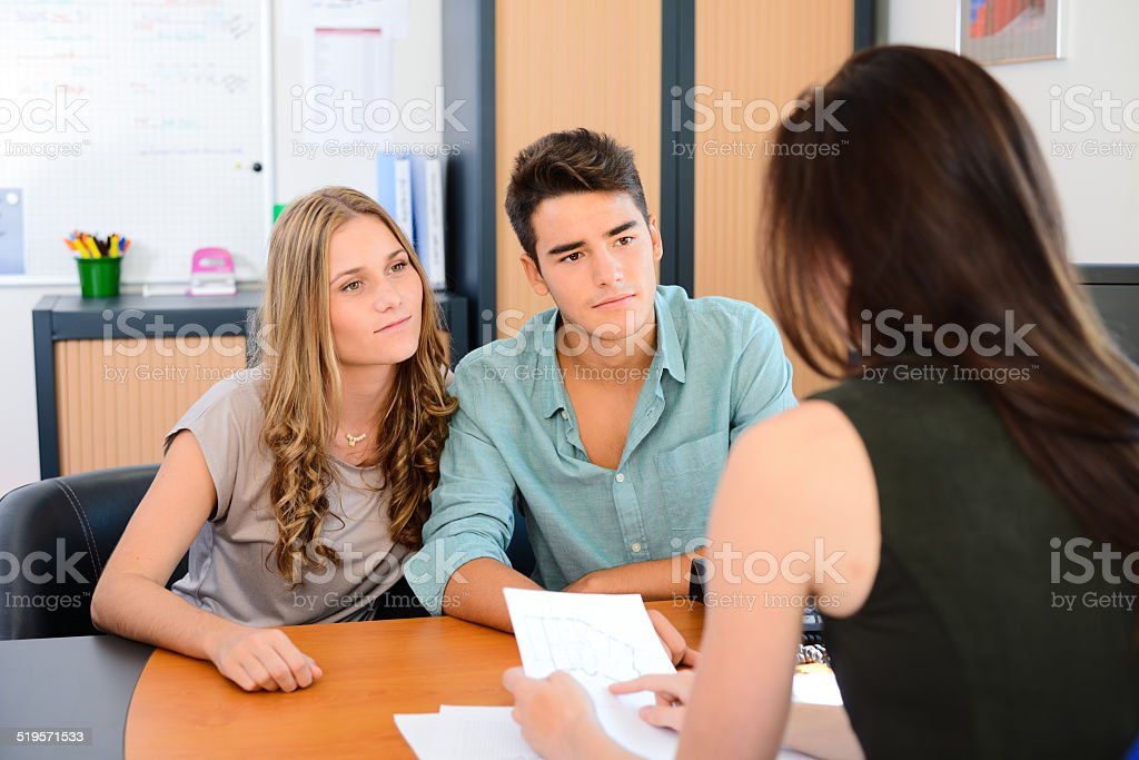happy young couple getting advice in office with beautiful business...